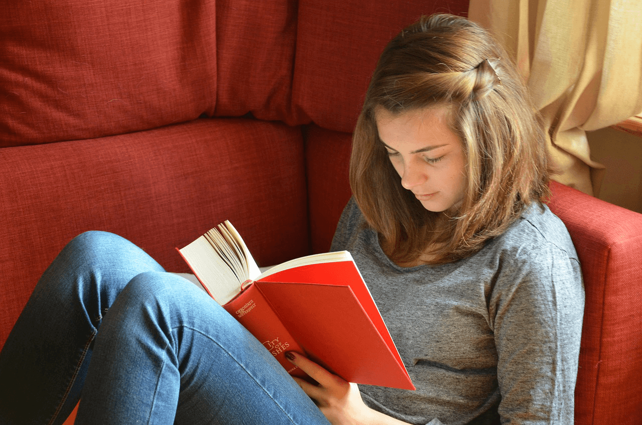 Student is reading a book on a couch