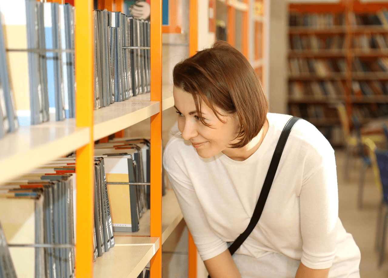 Womain is choosing a book in a library