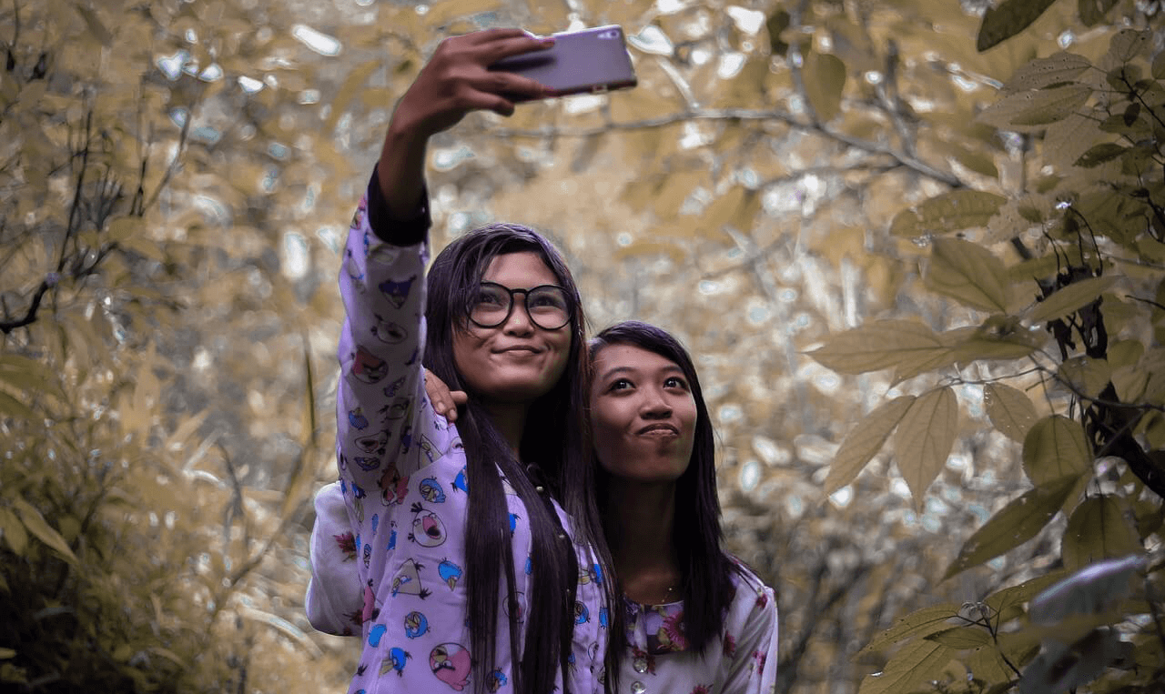 Girls are taking selfie in a wood