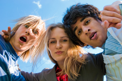 Three students looking in a camera.