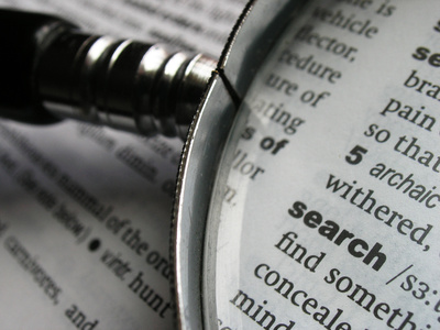 Magnifying glass on dictionary page with the word 'search'.