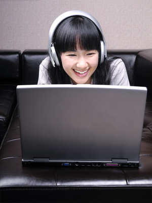 Enjoying Asian Girl with Laptop and Headphones
